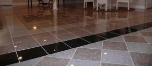 Yleiskuva kiiltävästä lattiasta, jossa on käytetty useita erivärisiä graniittilaattoja, jotka ovat järjestellyt riviin koristeellisesti neliöinä.